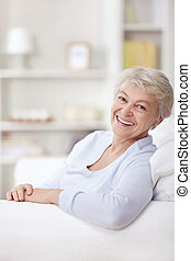 Laughing woman - Smiling elderly woman at home on the couch