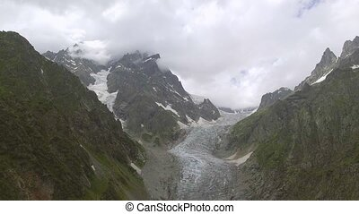 Flying over Glacier valley in svaneti Rocks. Snow peak in...