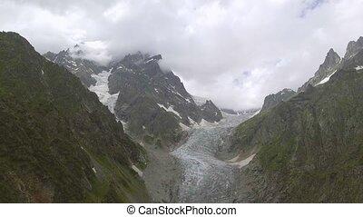 Flying over Glacier valley in svaneti Rocks. Snow peak in...