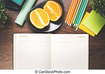 Empty hardcover notepad and fruit on desk - Top view of...