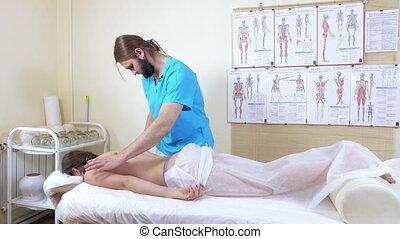 Diagnosis before a massage - Masseur man diagnoses a client...