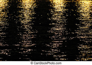 Water - Light rays reflected on a water surface in motion.