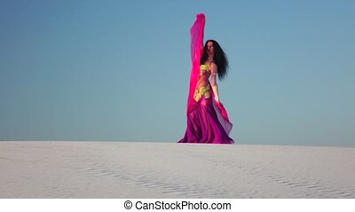 Girl with a veil in her hands dances a belly dance in the...