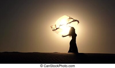 Girl on the sunset makes graceful movements. Slow motion ....