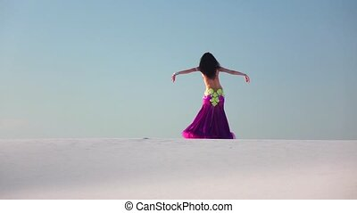 Graceful dancer against the sky dancing belly dance in a brilliant outfit. Slow motion