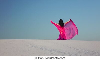Dancer in the sandy desert in the hands of a pink pink veil....