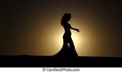 Girl performs beautiful belly dance on sunset background....
