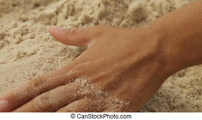 The girl takes the sea sand in her hand