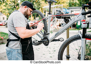 Bicycle mechanic repair front speed shifter. Cycle workshop...