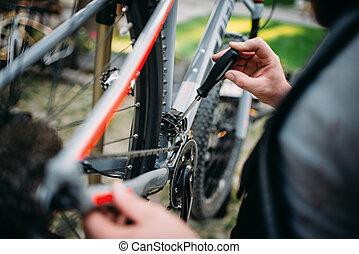 Hands with screwdriver repair shifter, bike repair - Male...