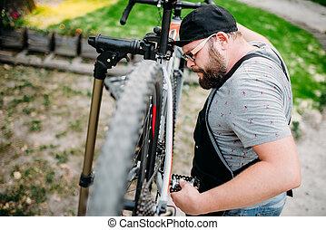 Repairman works with bike wheel, cycle workshop outdoor....