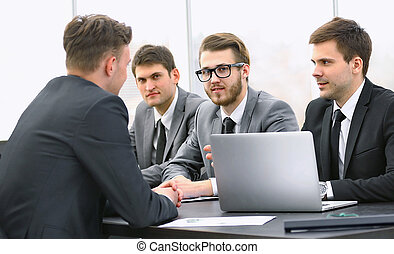 businessman talking to a business team at a Desk -...