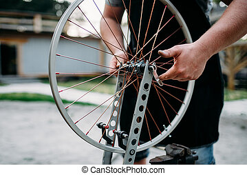 Male person adjusts bike spokes and wheel - Male person in...