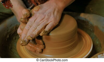 Professional male potter making bowl in pottery workshop,...