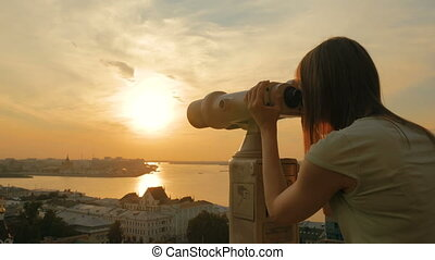 Young woman looking through tourist telescope, exploring...