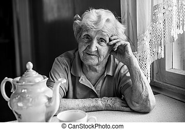 Portrait of elderly woman sitting at the table with tea.