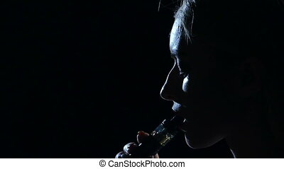 Girl smokes an electronic cigarette. Black background. Close...