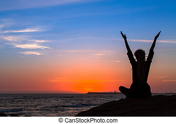 Silhouette of woman practicing yoga on the beach at amazing sunset.