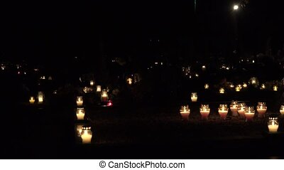 candle light on grave tombstone in city cemetery in night....