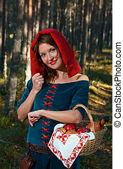 red Riding hood standing in a wood . beautiful girl in...