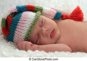 A sleeping baby girl wearing a striped hat