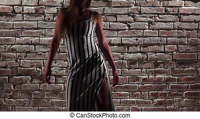 Girl charming in heels dancing to twerk against a brick...