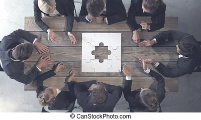 Business people and puzzle on wooden table, business problem...
