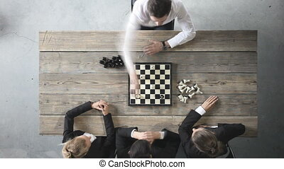 Business people playing chess, team of workers losing,...