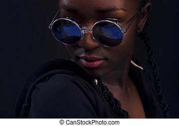 Close-up of woman with dark skin wearing round sunglasses -...