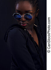 Cool young woman with dark skin wearing round sunglasses -...