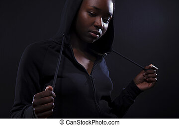 Cool and pensive woman with dark skin and attitude wearing...