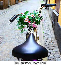 Bicycle with bunch of flowers on handle bar in Stockholm,...