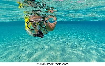 Snorkeling woman exploring beautiful ocean sealife,...