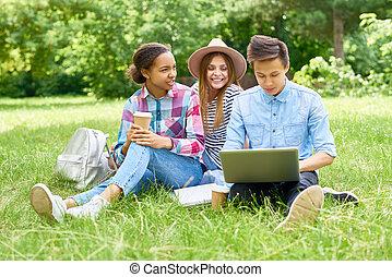 Group of  Happy Students Enjoying Break on  Lawn