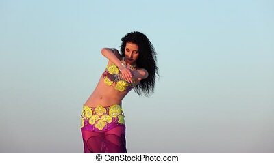 Graceful dancer against the sky dancing belly dance in a...