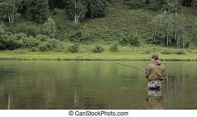 Joyful fisherman is fishing in calm river water near the...
