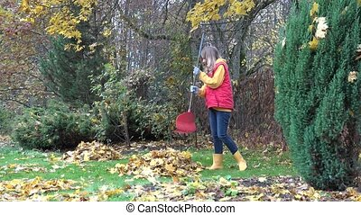 couple have fun raking autumnal leaves in garden. 4K - young...