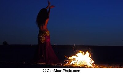 Late night a girl in the sand dancing belly dancing near a...
