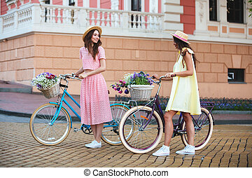 Young ladies standing outdoors with bicycles - Image of two...