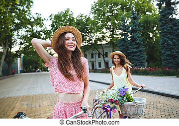 Two young happy ladies standing outdoors with bicycles -...