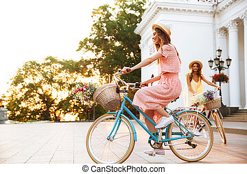 Two pretty smiling girls on a bicycle ride together