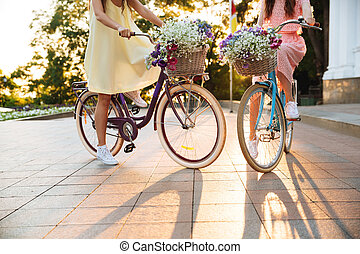 Cropped image of two young ladies walking on bicycles.