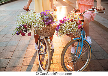 Cropped image of two young ladies on bicycles.