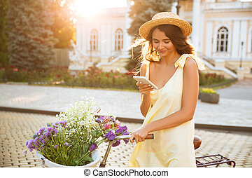 Smiling pretty girl in hat and dress using mobile phone...