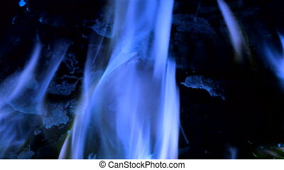 Intense blue flames blazing in fireplace. Burning woods...