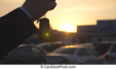 Male hands in suit giving keys of car to his friend at...