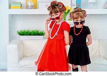 looking like mother - Two funny little girls with curlers in...