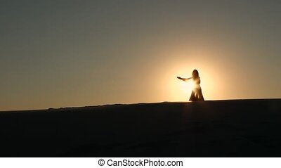 Girl performs a beautiful belly dance against the sunset,...