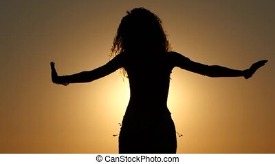 Girl dancing belly dancing on the beach against the sunset....