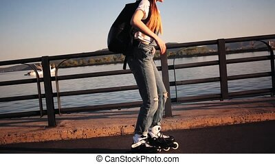 Young stylish funky girl riding roller skates a near sea...